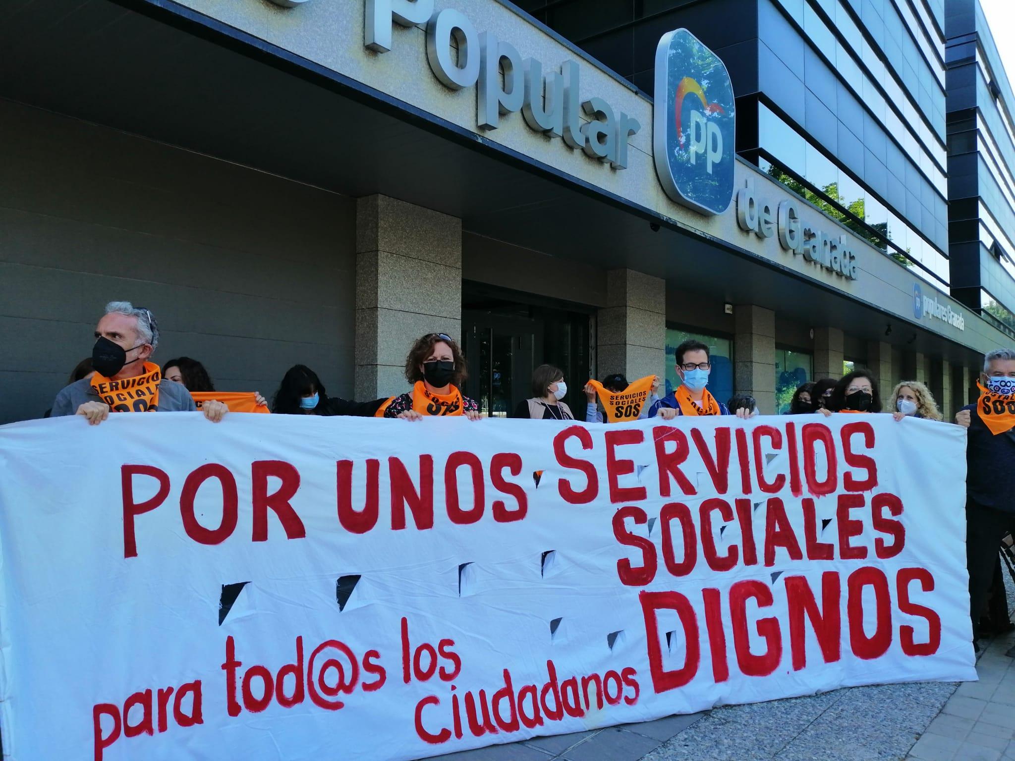 Los trabajadores de derechos sociales se manifiestan ante la sede el PP por unos servicios sociales dignos